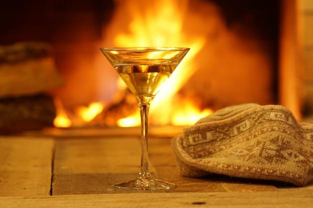Glasmartini gegen gemütlichen kaminhintergrund, winterferien