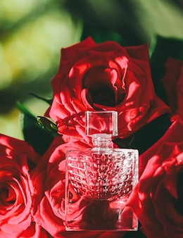 Glasparfümflasche in der parfümerie mit roten rosen als luxusgeschenkschönheits-flatlay-hintergrund und kosmetikpr...