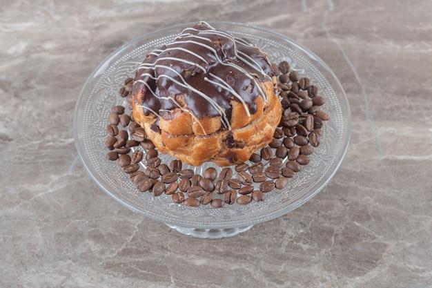 Glasplatte mit kaffeebohnen-schokoladenkuchen auf marmoroberfläche