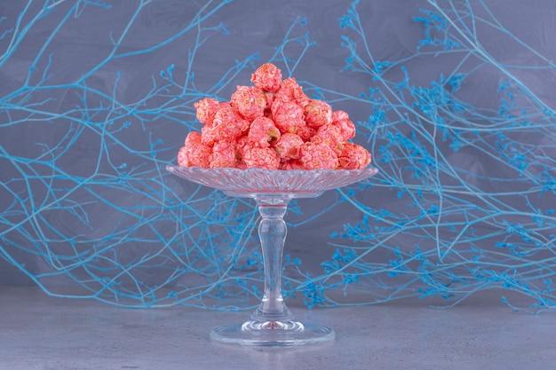 Glasplatte mit rosa popcornkugeln auf steinoberfläche