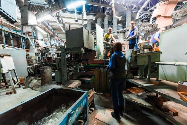 Glasproduktionsarbeiter, der mit industrieausrüstung auf fabrik arbeitet