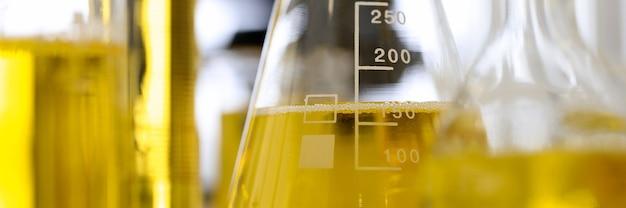 Glasreagenzgläser und -kolben stehen auf dem tisch in der nahaufnahme des pharmazeutischen labors. untersuchung der chemischen zusammensetzung des erdölproduktkonzepts.