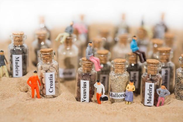 Glasreagenzglas mit sand verschiedener sommerferienorte. das hotel liegt im sand mit kleinen figuren.