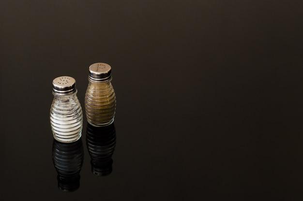 Glassalz- und pfefferstreuer auf schwarzem hintergrund