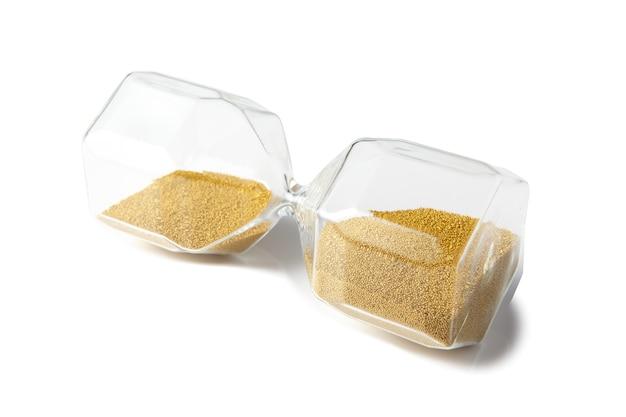 Glassanduhr mit goldenem sand, der auf seiner seite liegt
