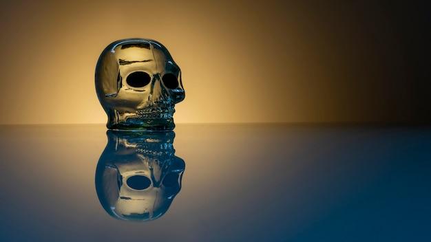 Glasschädel mit reflexion auf dem tisch. halloween