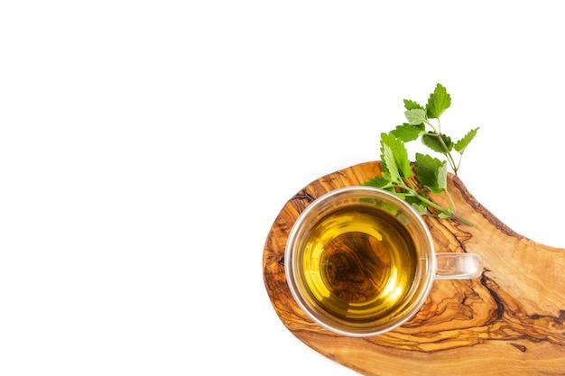 Glasschale heißer grüner tee mit minze auf holzständer