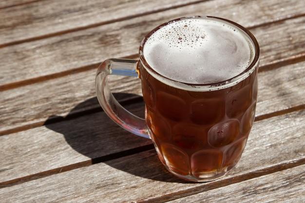 Glasschale kaltes bier auf einer holzoberfläche an einem heißen sonnigen tag