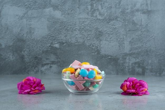 Glasschale mit buntem kaugummi mit blumen auf steinoberfläche.