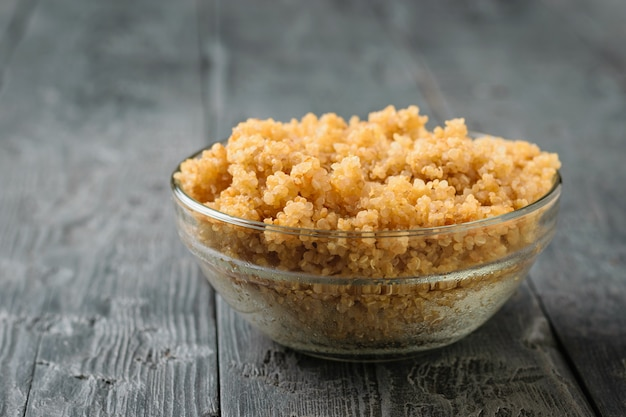 Glasschale mit der gekochten quinoa auf einem schwarzen holztisch. eine glutenfreie gekochte müslischale. gesunde vegetarische ernährung.