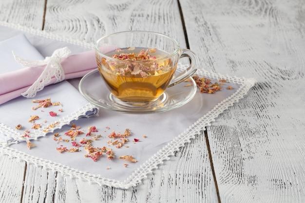 Glasschale mit frischem grünem tee und trockenen rosen