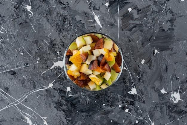 Glasschale mit frischem obstsalat auf marmoroberfläche.