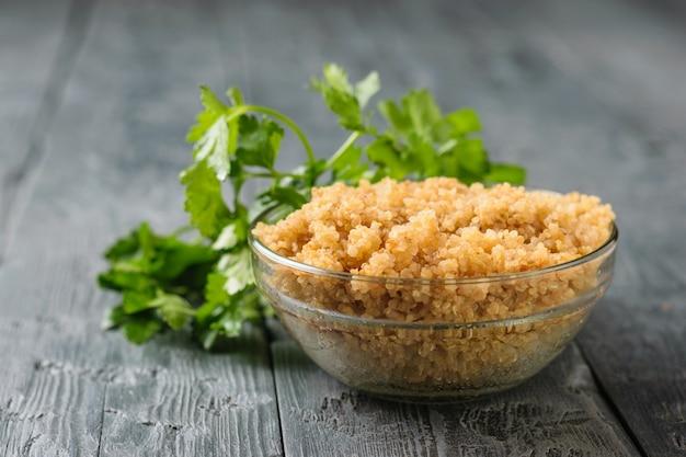 Glasschale mit gekochtem quinoa-müsli auf einem schwarzen holztisch