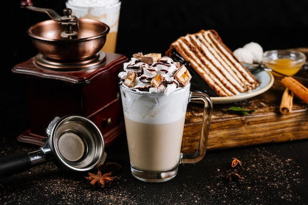 Glasschale mit kaffee mit sahne und schokolade auf schwarz