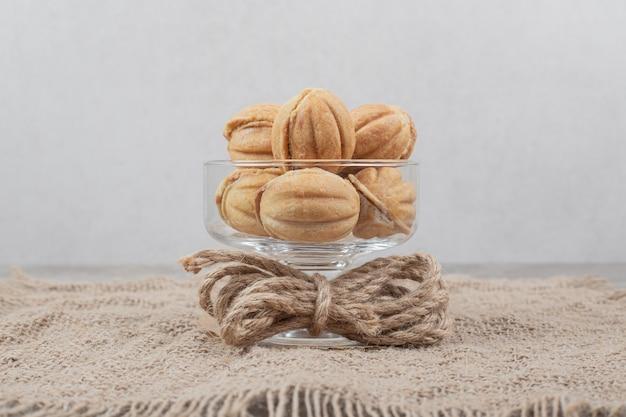 Glasschale mit walnussförmigen keksen auf sackleinen. hochwertiges foto