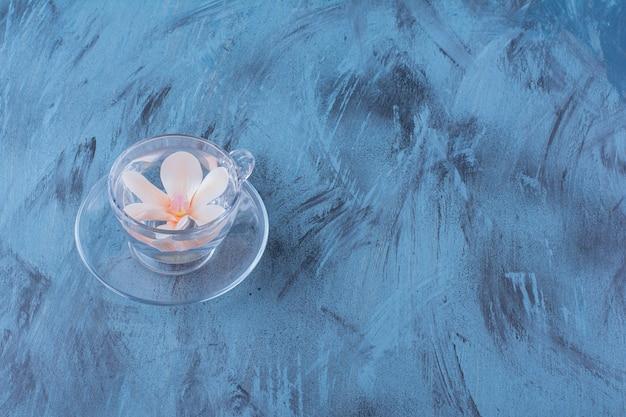 Glasschale mit wasser und rosa blume auf blau.