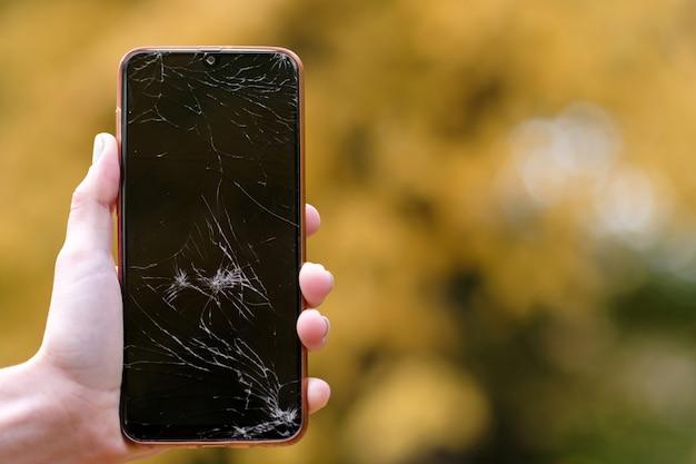 Glasscherben auf dem telefonbildschirm. gebrochenes telefon in der hand einer frau. herbst unscharfer blätter hintergrund