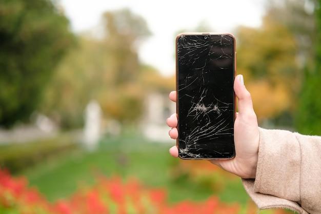 Glasscherben auf dem telefonbildschirm. gebrochenes telefon in der hand einer frau. hintergrund von pflanzen im park. unscharfer hintergrund