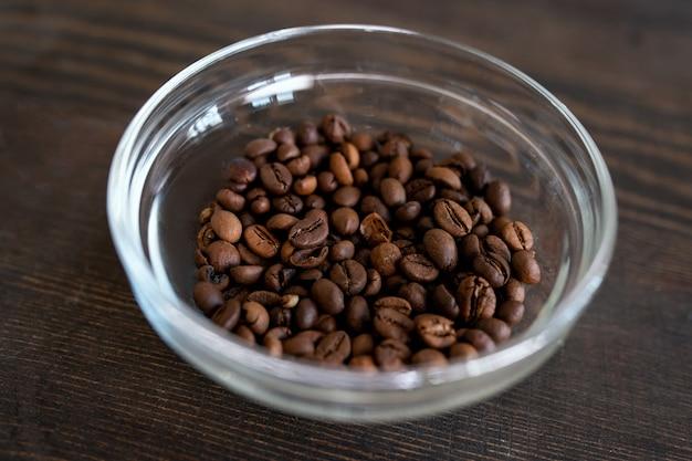 Glasschüssel mit gerösteten kaffeebohnen auf holztisch, vorbereitet zum mahlen vor der herstellung hausgemachter naturkosmetikprodukte