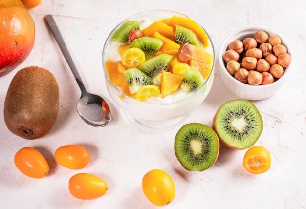 Glasschüssel mit joghurt und früchte, metallischer löffel und schüssel nüsse auf weißer tabelle.
