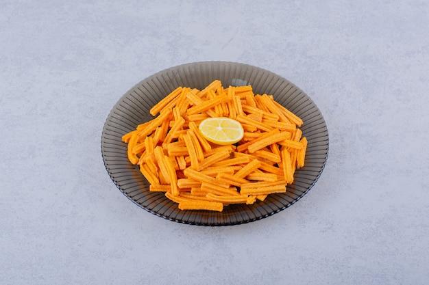 Glasschüssel mit knusprigen kartoffelchips auf stein.