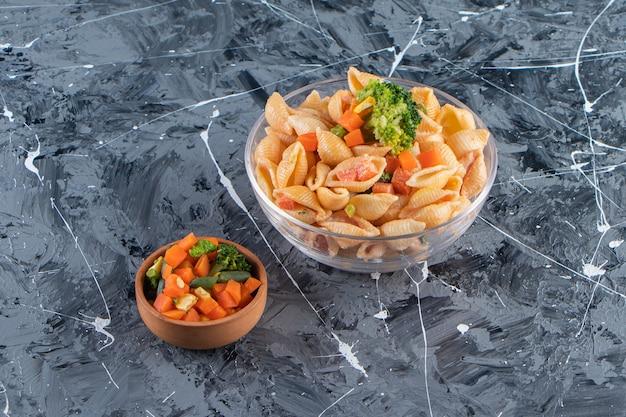 Glasschüssel mit leckeren muschelnudeln mit frischem salat auf marmoroberfläche.