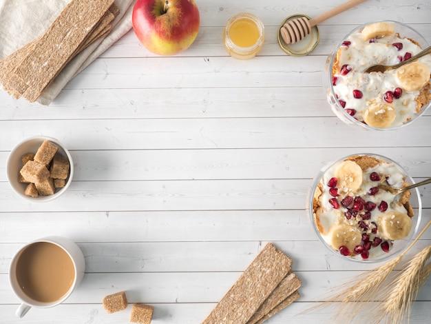 Glasschüssel mit müsli und joghurt mit banane, granatapfelsamen.