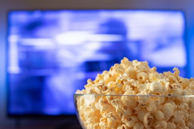 Glasschüssel mit popcorn und funktionierendem fernsehapparat.