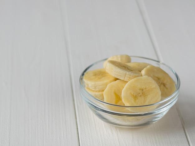 Glasschüssel mit scheiben der banane auf weißer draufsicht des holztischs.