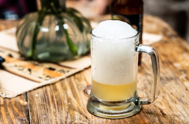 Glastasse bier mit schaum auf dem holztisch