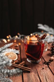 Glastasse glühwein auf holztisch und hintergrundweihnachtszeitkonzept