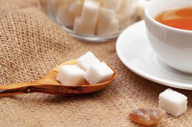 Glastasse heißer tee mit zucker auf dem tisch