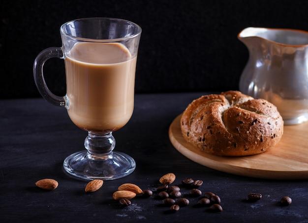 Glastasse kaffee mit sahne und brötchen auf einer schwarzen tabelle.