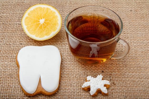 Glastasse tee, stück zitrone und lebkuchen in zahn- und sternform auf dem tisch mit sackleinen.