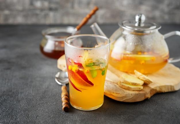 Glastasse tee und teekannenzusammensetzung auf grauer oberfläche