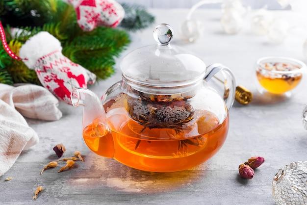 Glasteekanne mit blumen gebundenem tee, heißem tee in glasteekanne und honig mit metallhonigstock