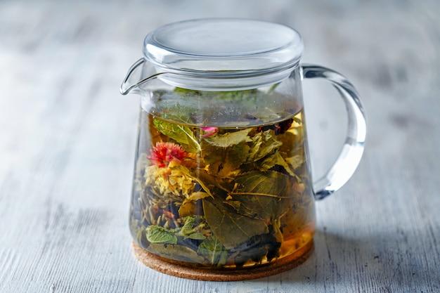 Glasteekanne mit exotischem grünem tee auf holztisch
