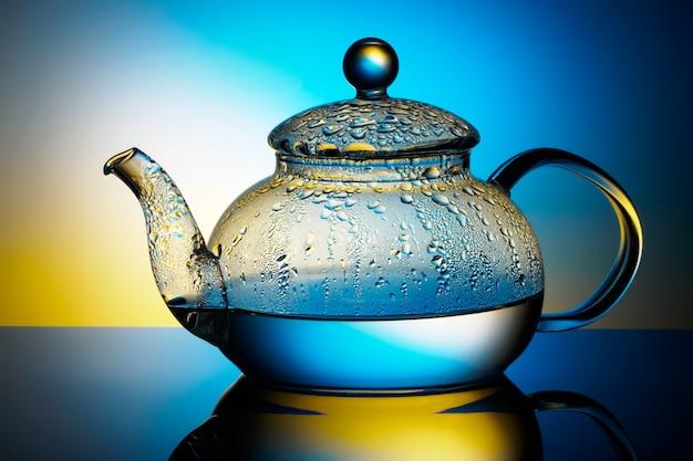 Glasteekanne mit kochendem wasser und tropfen kondensation