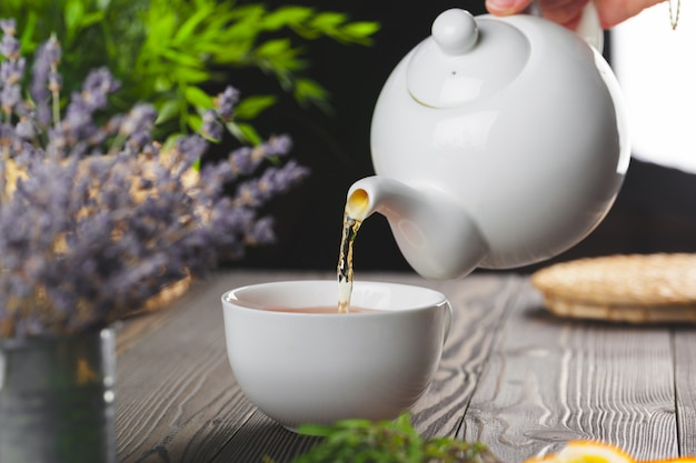 Glasteekanne mit schale schwarzem tee auf holztisch