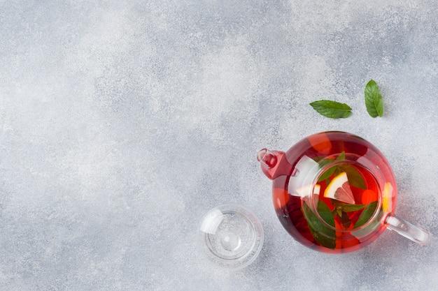 Glasteekanne mit tee, minze und zitrone auf grauer tabelle mit kopienraum