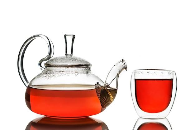 Glasteekanne und glas mit tee getrennt auf weiß mit reflexion.