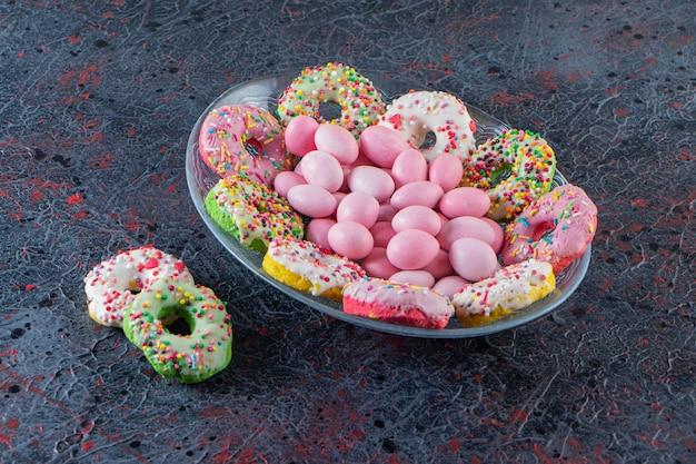 Glasteller mit bunten leckeren donuts und rosa bonbons auf dunkler oberfläche.