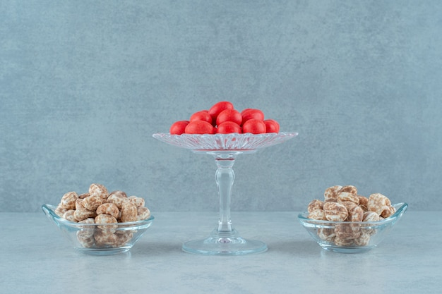 Glasteller voller leckerer lebkuchen und roter süßer bonbons auf weißer oberfläche