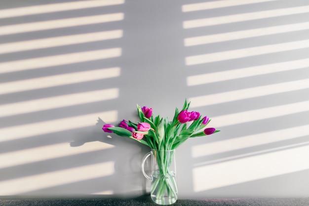 Glasvase mit blumenstrauß von schönen tulpen auf grauer wand