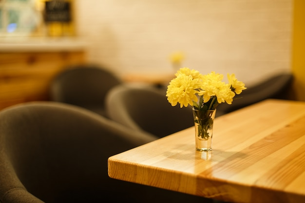 Glasvase mit gelber frischer blume auf holztisch