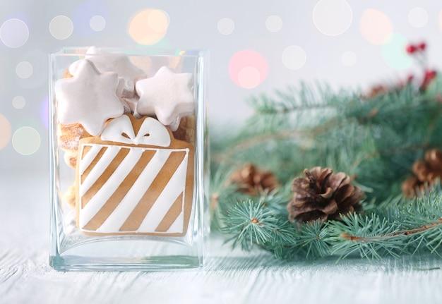 Glasvase mit leckeren weihnachtsplätzchen und koniferenzweig auf hellem holztisch