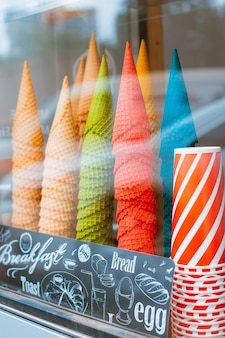 Glasvitrine in einer eisdiele mit vielen kegeln für eistüten. erfrischendes sommeressen im heat street fast food zum mitnehmen