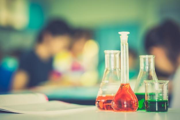 Glaswarenlabor auf tabelle auf den unscharfen studenten, die im labor lernen und studieren