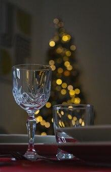 Glasweinglas mit weihnachtsdekoration. nahaufnahme des tisches