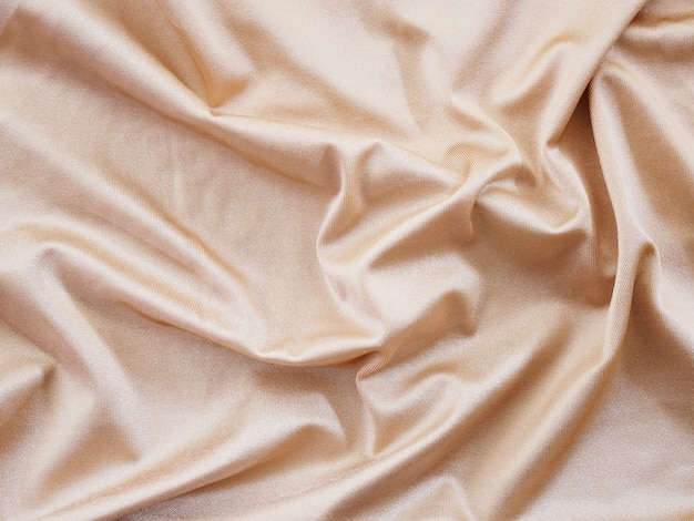 Glatte beige seiden- oder satin-luxusstruktur für hochzeitshintergrund.
